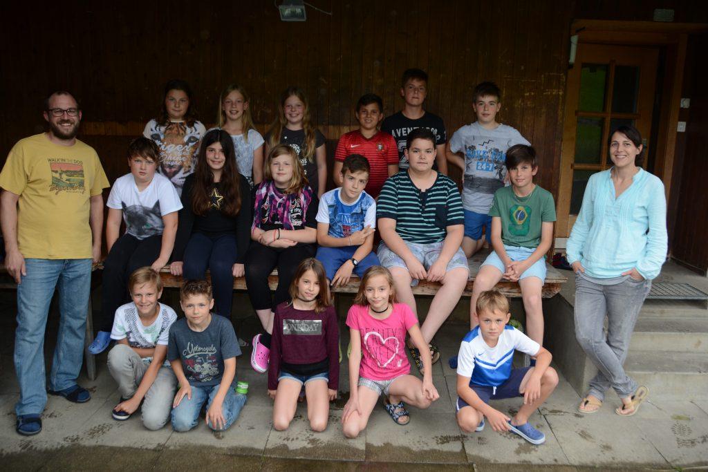Die Lehrpersonen Mike Surer und Andrea Goumas zusammen mit ihren Schüler vor dem Lagerhaus. Bild: Werner Lenzin